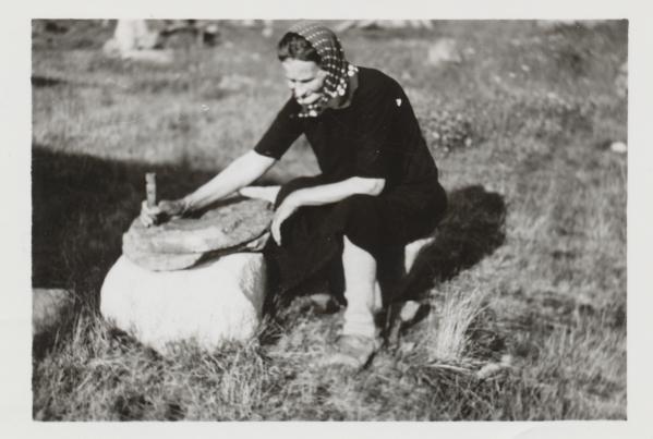 Hilma Kataja esittelee pihamaallaan käsikiven käyttöä